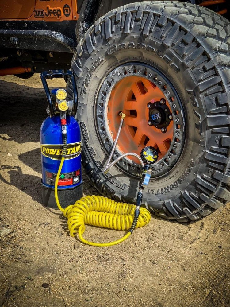 Candy Blue 10lb Power Tank next to a Jeep tire