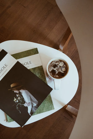 Photo by Taisiia Shestopal on Unsplash two Console magazines flat lay on a white table with wooden flooring in the background with an iced coffee on the table