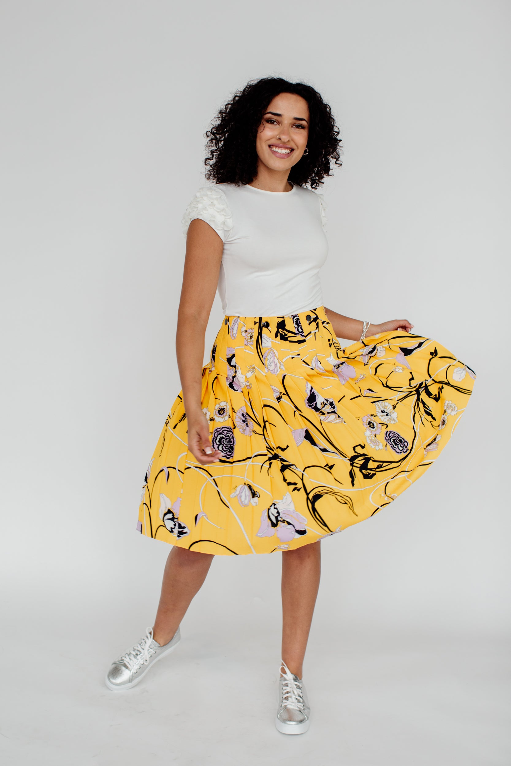 A woman in a yellow skirt dances.