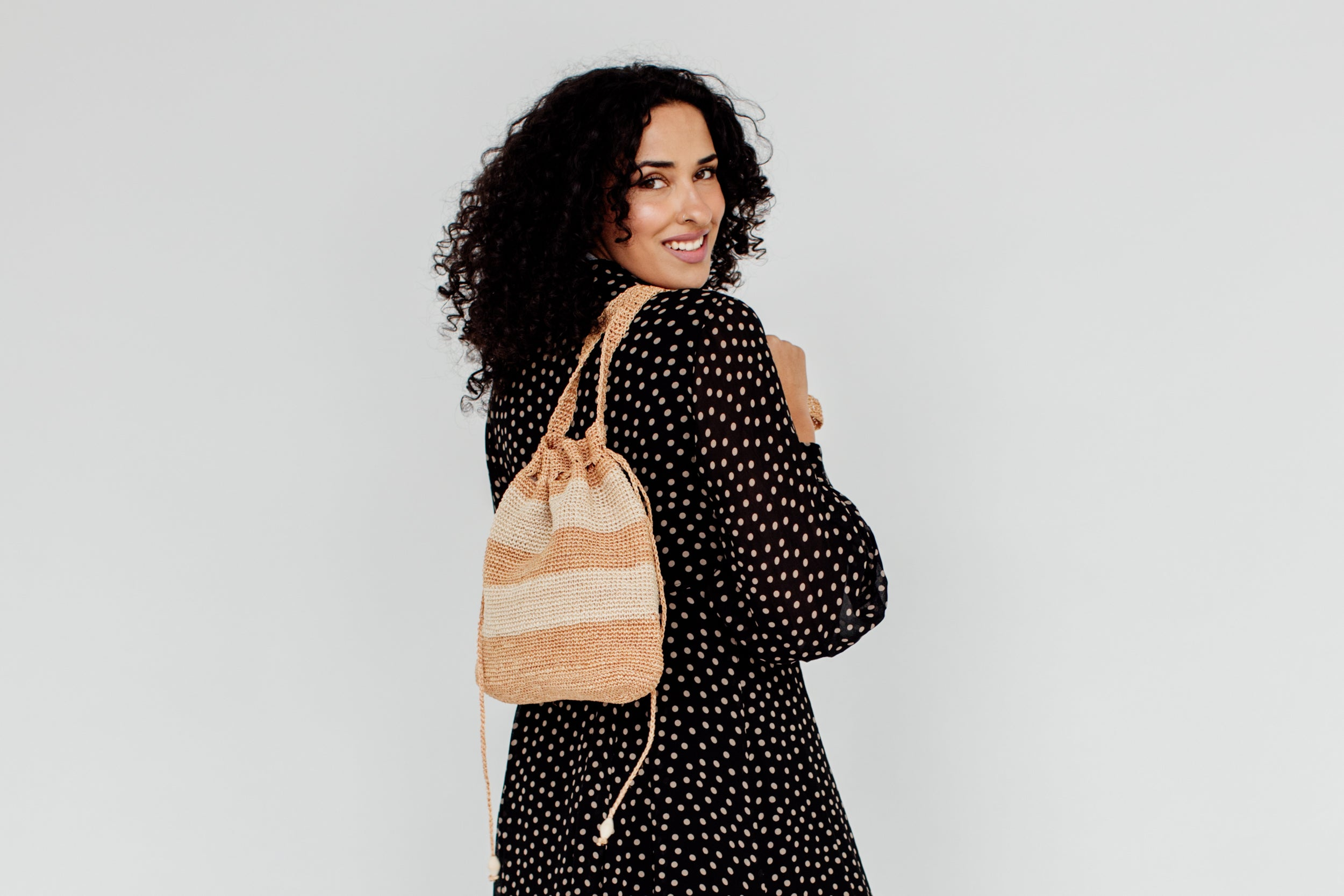 A woman holds a bag over her shoulder and smiles.