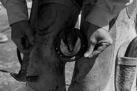 Photo of a farrier working on a horse hoof with smoke