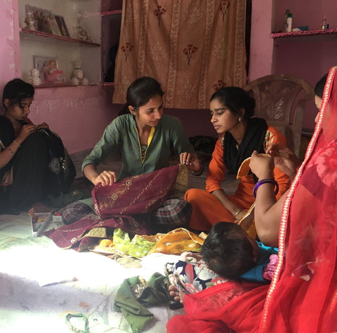 indian women sewing on the floor