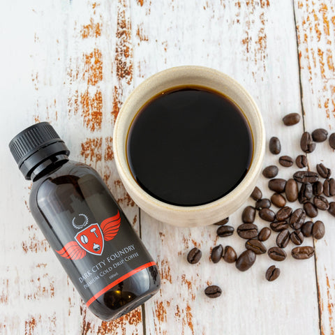 100ml bottle of cold brew coffee next to a mug of coffee. Flatlay with some coffee beans scattered around the mug