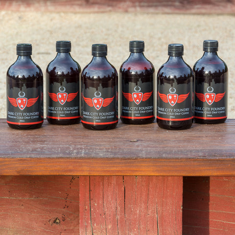 6 pack of 500ml bottles of cold brew coffee lined up in a row at the park.