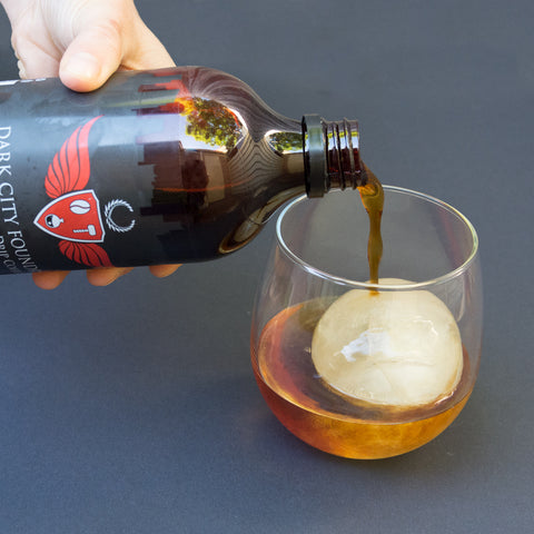 pouring cold brew coffee into a glass over ice.