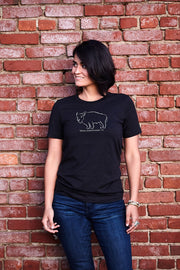 Bison Americanus black heather, short sleeve, crew neck tee, t-shirt with gray hand-printed design of bison and Bison Americanus saying underneath of image on female model in front of brick wall. A pair of socks will be donated to a featured shelter through our Buy One, Give a Pair program. Common Interest Clothing.