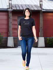 Bison Americanus black heather, short sleeve, crew neck tee, t-shirt with gray hand-printed design of bison and Bison Americanus saying underneath of image on female model walking in front of building. A pair of socks will be donated to a featured shelter through our Buy One, Give a Pair program. Common Interest Clothing.