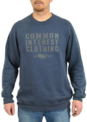 C.I.C. heather navy, long sleeve, fleece lined, crew neck tee, sweatshirt with dark gray hand-printed design of the words Common Interest Clothing EST 2018 and a silhouette of the USA. A pair of socks will be donated to a featured shelter through our Buy One, Give a Pair program. Common Interest Clothing.