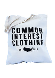 Common Interest Clothing logo bag with established in 2018 notation around US silhouette. Natural canvas cotton library bag. Uniquely American Clothing that Matters.