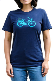 Cruiser navy, short sleeve, crew neck tee, t-shirt with light blue hand-printed design of beach cruiser bicycle with Common Interest Clothing shaped as a package on the back. A pair of socks will be donated to a featured shelter through our Buy One, Give a Pair program. Common Interest Clothing.