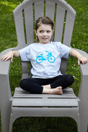 Kid's Cruiser athletic heather, short sleeve, crew neck tee, t-shirt with light blue hand-printed design of beach cruiser bicycle with Common Interest Clothing shaped as a package on the back. A pair of socks will be donated to a featured shelter through our Buy One, Give a Pair program. Common Interest Clothing.