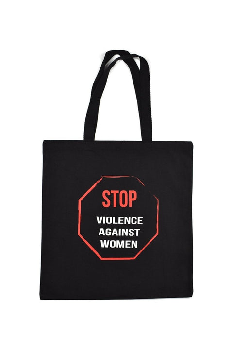 Enough black canvas library bag with red and white hand printed design stating Stop Violence Against Women in the shape of a stop sign. Donation goes to the Joyful Heart Foundation. Buy One Give a Pair donation of socks to a featured shelter with every item sold. Common Interest Clothing