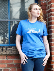 Ninth Tour heather true royal blue, short sleeve, crew neck tee, t-shirt with light gray hand-printed design of a pave hawk helicopter and the word Freedom in script above the propellers on female model. A pair of socks will be donated to a featured shelter through our Buy One, Give a Pair program with every item purchased. Common Interest Clothing.