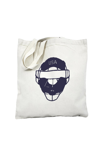 Full count natural canvas library bag with navy ink of a catcher's mask with USA on the top. Buy One Give a Pair donation of socks to a featured shelter with every item sold. Common Interest Clothing