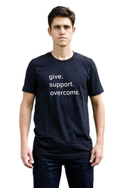 G.S.O black heather, short sleeve, crew neck tee, t-shirt with white hand-printed design of the words give, support, overcome on male model. Donation goes to the Covenant House. Buy One Give a Pair donation of socks to a featured shelter with every item sold. Common Interest Clothing