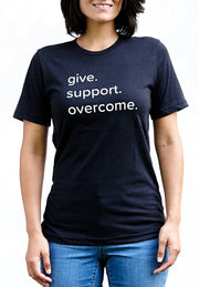 G.S.O black heather, short sleeve, crew neck tee, t-shirt with white hand-printed design of the words give, support, overcome on female model. Donation goes to the Covenant House. Buy One Give a Pair donation of socks to a featured shelter with every item sold. Common Interest Clothing