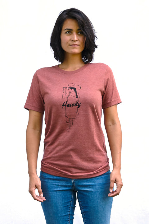 Howdy heather clay, short sleeve, crew neck tee, t-shirt with black hand-printed design of cowgirl in a sundress, boot and a cowboy hat. A pair of socks will be donated to a featured shelter through our Buy One, Give a Pair program with every item purchased. Common Interest Clothing.