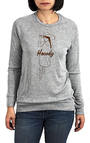 Howdy athletic heather, long sleeve, crew neck lightweight sweater with chocolate brown hand-printed design of cowgirl in a sundress, boot and a cowboy hat. A pair of socks will be donated to a featured shelter through our Buy One, Give a Pair program with every item purchased. Common Interest Clothing.