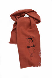 Howdy rust scarf with black hand-printed design of cowgirl in a sundress, boot and a cowboy hat. A pair of socks will be donated to a featured shelter through our Buy One, Give a Pair program with every item purchased. Common Interest Clothing.