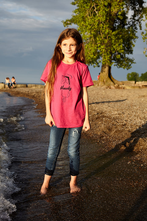 Kid's Howdy berry, short sleeve, crew neck tee, t-shirt with black hand-printed design of cowgirl in a sundress, boot and a cowboy hat. A pair of socks will be donated to a featured shelter through our Buy One, Give a Pair program with every item purchased. Common Interest Clothing.
