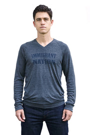 Immigrant Nation dark gray heather lightweight sweater with navy hand-printed design of the words Immigrant Nation and a small star in the middle. A pair of socks will be donated to a featured shelter through our Buy One, Give a Pair program with every item purchased. Common Interest Clothing.