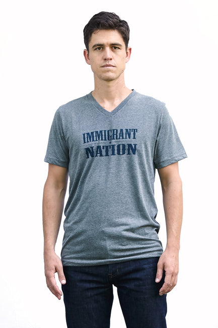 Immigrant Nation deep heather, short sleeve, v-neck tee, t-shirt with navy hand-printed design of the words Immigrant Nation and a small star in the middle. A pair of socks will be donated to a featured shelter through our Buy One, Give a Pair program with every item purchased. Common Interest Clothing.