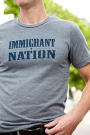 Immigrant Nation deep heather, short sleeve, crew neck tee, t-shirt with navy hand-printed design of the words Immigrant Nation and a small star in the middle. A pair of socks will be donated to a featured shelter through our Buy One, Give a Pair program with every item purchased. Common Interest Clothing.