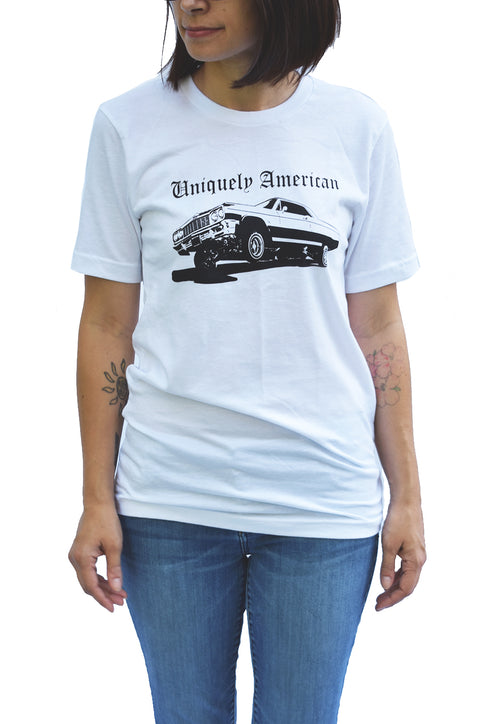 Low Rider white short sleeve tee with black hand printed design of car on hydraulics and the words Uniquely American written above the car. Uniquely American Clothing that Matters.