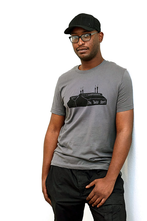 Rust Belt asphalt, short sleeve, crew neck tee, t-shirt with black hand-printed design of a steel mill and the words The Third Shift along the bottom of the mill on male model with hat. A pair of socks will be donated to a featured shelter through our Buy One, Give a Pair program with every item purchased. Common Interest Clothing.