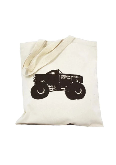 Monster Truck natural canvas library bag with chocolate ink of a monster truck and the words Common Interest Clothing on the side as a logo. Buy One Give a Pair donation of socks to a featured shelter with every item sold. Common Interest Clothing