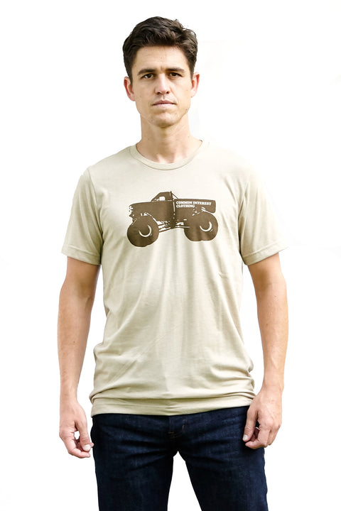 Monster Truck heather tan, short sleeve, crew neck tee with chocolate hand-printed design of a monster truck and the word Common Interest Clothing along the side of the design. A pair of socks will be donated to a featured shelter through our Buy One, Give a Pair program with every item purchased. Common Interest Clothing.