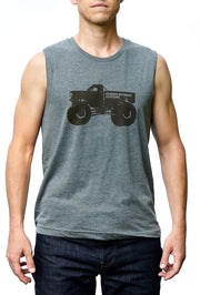 Monster Truck deep heather gray, sleeveless, muscle tee, crew neck, muscle shirt with chocolate hand-printed design of a monster truck and the word Common Interest Clothing along the side of the design. A pair of socks will be donated to a featured shelter through our Buy One, Give a Pair program with every item purchased. Common Interest Clothing.