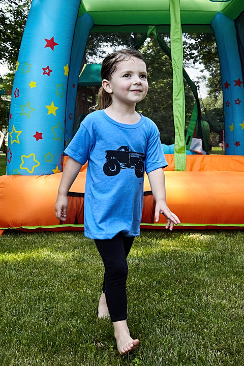 Kid's Monster Truck heather blue, short sleeve, crew neck tee with black hand-printed design of a monster truck and the word Common Interest Clothing along the side of the design. A pair of socks will be donated to a featured shelter through our Buy One, Give a Pair program with every item purchased. Common Interest Clothing.