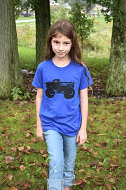 Kid's Monster Truck royal blue, short sleeve, crew neck tee with black hand-printed design of a monster truck and the word Common Interest Clothing along the side of the design. A pair of socks will be donated to a featured shelter through our Buy One, Give a Pair program with every item purchased. Common Interest Clothing.