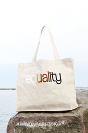 Color blind natural canvas gusset bag with skin color blended hand-print of the word equality for racial equality on a rock on the water. Donation goes to the Equal Justice Initiative. Buy One Give a Pair donation of socks to a featured shelter with every item sold. Common Interest Clothing