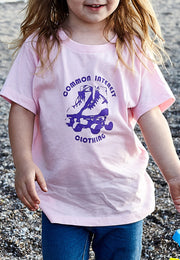 Kid's Roller Rama pink, short sleeve, crew neck tee, t-shirt with purple hand-printed design of roller skates and the words Common Interest Clothing around the image. A pair of socks will be donated to a featured shelter through our Buy One, Give a Pair program. Common Interest Clothing.