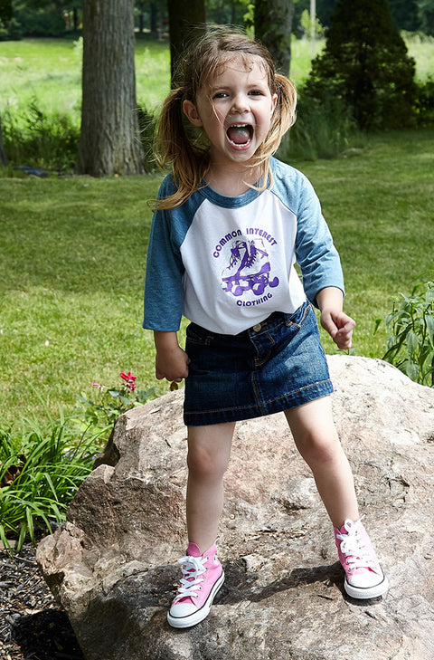Kid's Roller Rama white and denim baseball, raglan, 3/4 sleeve, crew neck tee, t-shirt with purple hand-printed design of roller skates and the words Common Interest Clothing around the image. A pair of socks will be donated to a featured shelter through our Buy One, Give a Pair program. Common Interest Clothing.