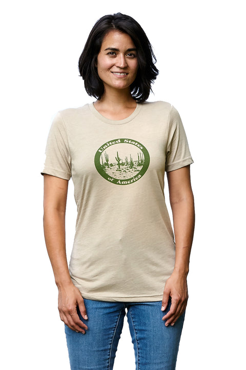 Saguaro heather tan, short sleeve, crew neck tee, t-shirt with forest green hand-printed design of a desert landscape inside of a circular seal with United States of America around the outside. A pair of socks will be donated to a featured shelter through our Buy One, Give a Pair program. Common Interest Clothing.