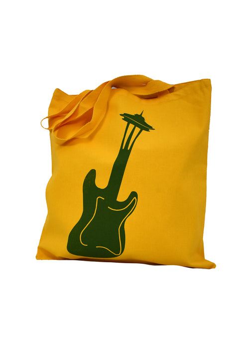 Seattle Sound gold canvas library bag with hunter green hand-printed design of a guitar turning into the Seattle Space Needle. A pair of socks will be donated to a featured shelter through our Buy One, Give a Pair program with every item purchased. Common Interest Clothing.