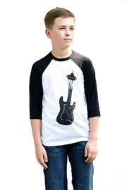 Kid's Seattle Sound white and black, raglan, 3/4 sleeve, crew neck, baseball tee, t-shirt with black hand-printed design of a guitar turning into the Seattle Space Needle. A pair of socks will be donated to a featured shelter through our Buy One, Give a Pair program with every item purchased. Common Interest Clothing.