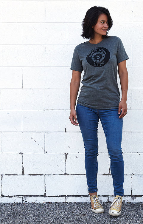 Tread deep heather gray, short sleeve, crew neck tee, t-shirt with black hand-printed design of a tire and the words Common Interest Clothing as the logo. A pair of socks will be donated to a featured shelter through our Buy One, Give a Pair program with every item purchased. Common Interest Clothing.