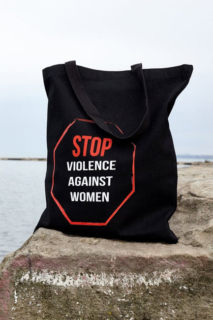 Enough black canvas library bag with red and white hand printed design stating Stop Violence Against Women in the shape of a stop sign on a rock on the water. Donation goes to the Joyful Heart Foundation. Buy One Give a Pair donation of socks to a featured shelter with every item sold. Common Interest Clothing