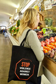 Enough black canvas library bag with red and white hand printed design stating Stop Violence Against Women in the shape of a stop sign on a model shopping at the market. Donation goes to the Joyful Heart Foundation. Buy One Give a Pair donation of socks to a featured shelter with every item sold. Common Interest Clothing