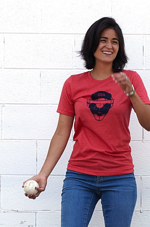 Full Count heather red, short sleeve, crew neck tee, t-shirt with navy design of baseball catcher's mask and the word USA in the top section of the image on female model standing in front of a wall preparing to throw a ball. A pair of socks will be donated to a featured shelter through our Buy One, Give a Pair program. Uniquely American Clothing that Matters. Common Interest Clothing