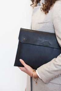 woman carrying eco-friendly black leather laptop bag
