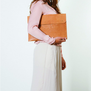 woman carrying eco-friendly brown leather laptop bag