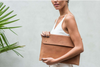 woman modeling eco-friendly brown leather laptop bag