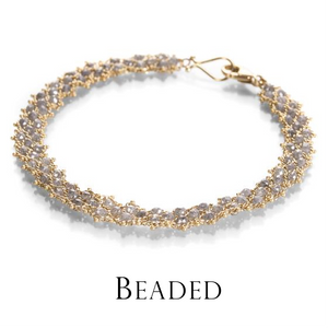 An 18k yellow gold, hand woven bracelet with gray diamond beads by the jewelry designer Sara Freedenfeld of Amali jewelry. Fine jewelry, designer jewelry, gray diamond bracelet, handcrafted bracelet, diamond bracelet, unique bracelets