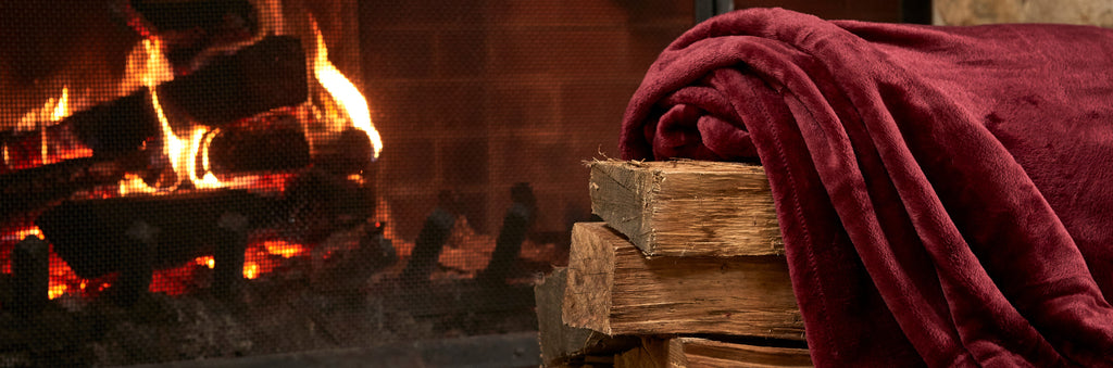 VelvetLoft Throw Blanket in Rustic Red by a fire place