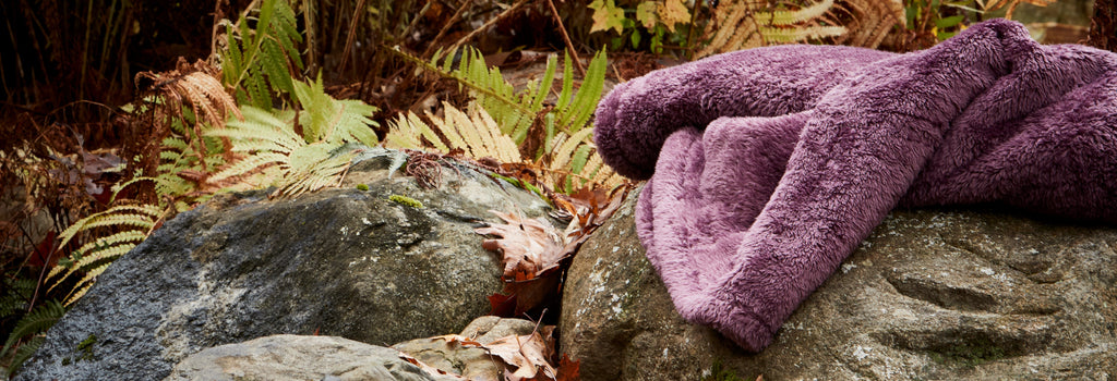 Ultimate Extra-Fluffy Throw in Purple Plum on a rock in the woods